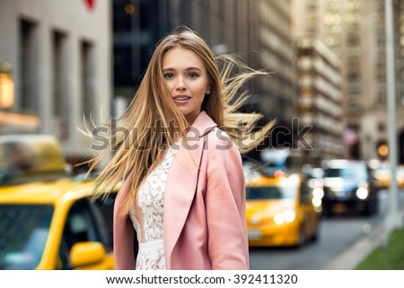 Portrait of blonde girl with flyaway hair in the background of New York City street with taxi cabs. Elegant businesswoman walking on city street. - stock photo
