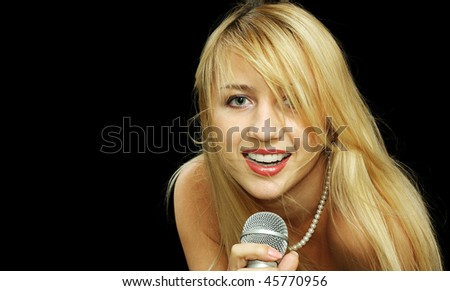 Portrait of blonde girl with naked shoulders singing in microphone, isolated on black
