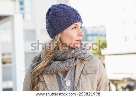 Portrait of blonde in warm clothes thinking in the city