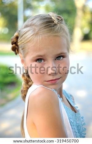Portrait of blonde little girl looks back outdoor - stock photo