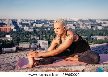Portrait of blonde strong woman in sportwear doing workout stretching on the roof of skyscraper above the big city at early morning. Female sporty muscular body. Dawn and sunrise bright sunny light.  - stock photo