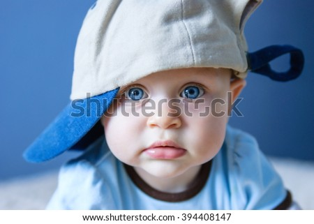 Portrait of blue-eyed baby with eyes wide open in the cap