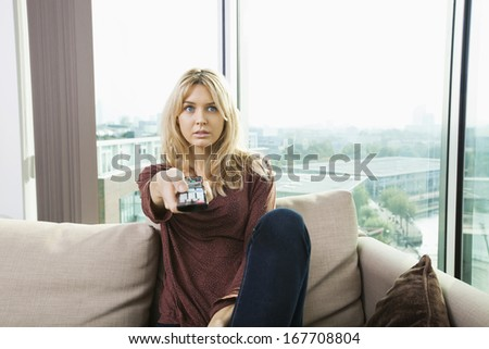 Portrait of blue eyed woman watching television on sofa at home - stock photo