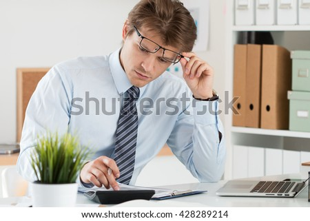 Portrait of bookkeeper or financial inspector adjusting his glasses making report, calculating or checking balance. Home finances, investment, economy, saving money or insurance concept - stock photo