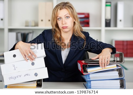 Portrait of bored mid adult businesswoman behind stacked binders at office desk - stock photo