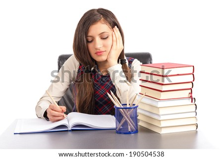 Portrait of  bored schoolgirl doing his homework at desk isolated over white background