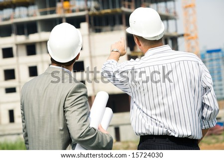 Portrait of boss pointing at construction with worker near by