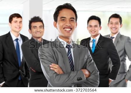 portrait of boss standing in front of his team, leading to success - stock photo