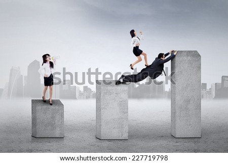 Portrait of bossy businesswoman giving instruction to her workers on business chart - stock photo
