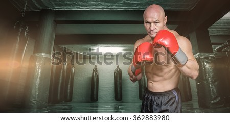 Portrait of boxer with gloves against red boxing area with punching bags - stock photo