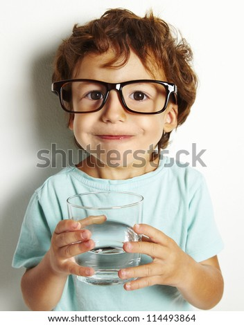 Portrait of boy drinking glass of water isolated in white - stock photo