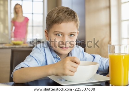 Portrait of boy having breakfast at table with mother standing in background - stock photo