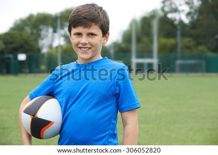 Portrait Of Boy Holding Ball On School Rugby Pitch - stock photo
