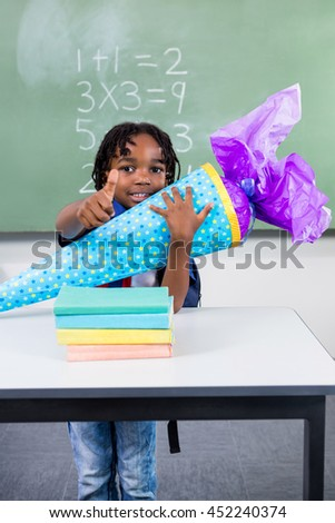 Portrait of boy holding gift at table in classroom - stock photo