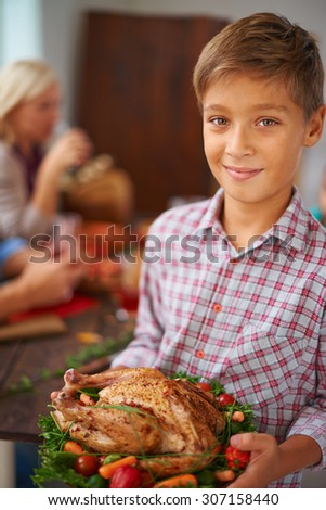 Portrait of boy holding roasted chicken - stock photo
