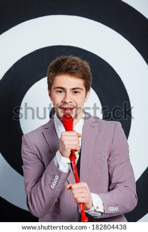 Portrait of boy in elegant jacket singing with microphone in studio - stock photo