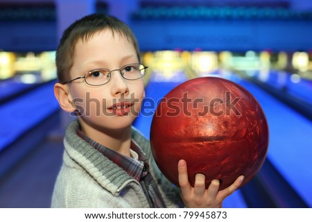 Portrait of boy in glasses, which hold ball for bowling - stock photo