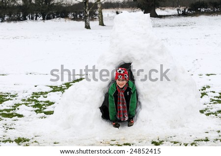 portrait of boy in snow igloo - stock photo