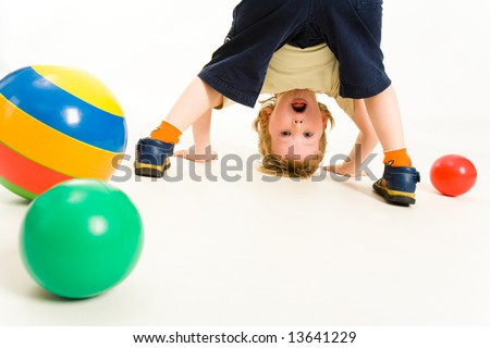 Portrait of boy looking at camera between his legs - stock photo
