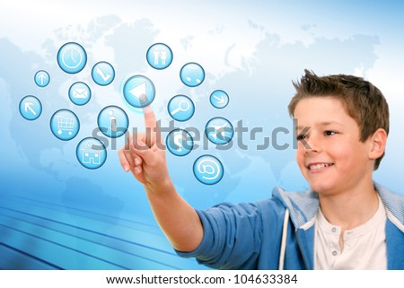 Portrait of Boy pointing at web icons with futuristic interface.