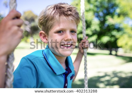 Portrait of boy sitting on a swing in the park on a sunny day