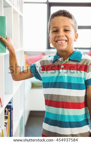 Portrait of boy taking a book from bookshelf in library at school