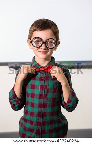 Portrait of boy tying bow while standing in classroom - stock photo