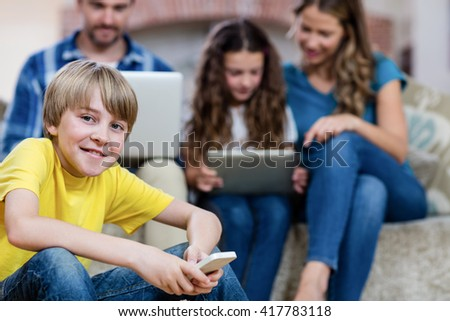 Portrait of boy using a mobile phone while family sitting on a sofa in background - stock photo