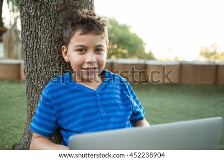 Portrait of boy using laptop while sitting at park