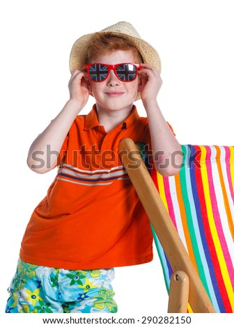 Portrait of Boy wearing a hat and sunglasses standing near beach chair. Isolated On White Background. - stock photo
