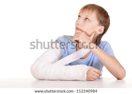 Portrait of boy with a broken arm on white background - stock photo