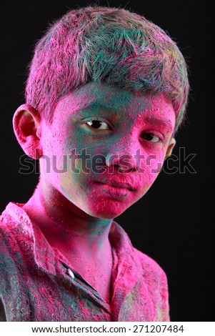 Portrait of boy with face smeared with colored powder in a dark background. Concept for Indian festival Holi. - stock photo