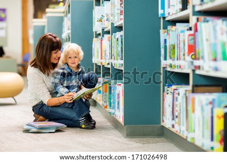 Portrait of boy with teacher reading book by bookshelf in library - stock photo
