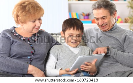 portrait of boy with their grandparents at home - stock photo