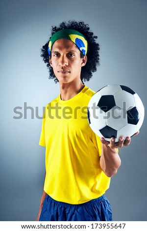 Portrait of Brazilian soccer football player with ball and national kit ready for the world cup