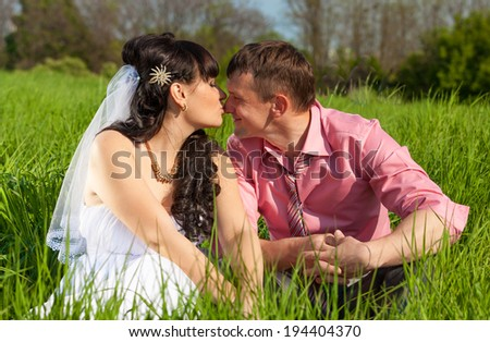 Portrait of bride and groom kissing in lips while sitting on meadow