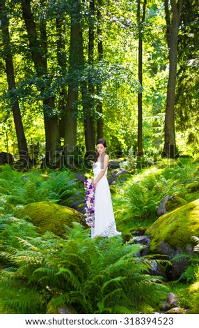 Portrait of bride holding her wedding flowers in a woods on a sunny day.