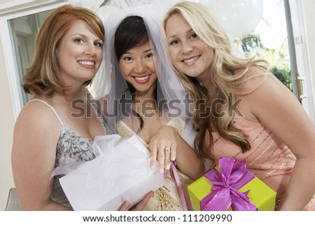 Portrait of bride showing her engagement ring with friends holding gifts
