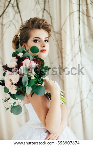 Portrait of bride with bouquet in Studio