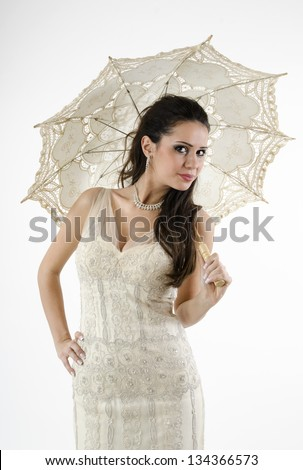 portrait of bride with long hair, make-up and jewelry in cream wedding dress standing with an umbrella in his hand