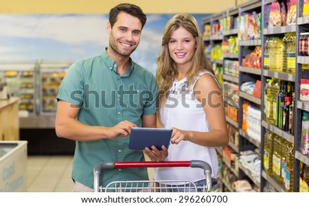Portrait of bright couple using digital tablet at supermarket - stock photo