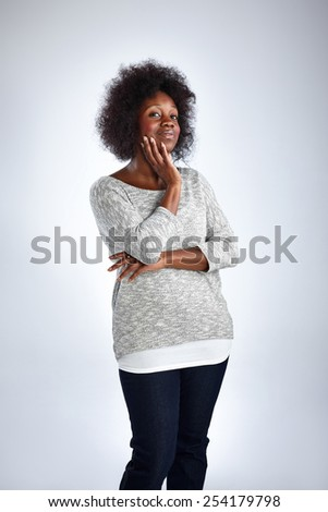 Portrait of british caribbean woman standing with her hand on chin looking away thinking over white background - stock photo