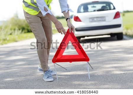 Portrait of broken down car owner spick up a red warning triangle. - stock photo