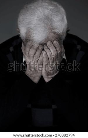 Portrait of broken down older man hiding face in hands - stock photo