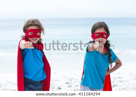 Portrait of brother and sister in superhero costume at beach - stock photo