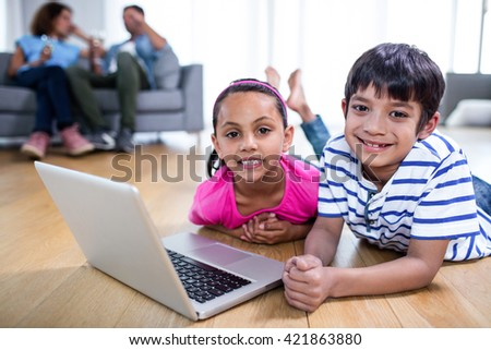 Portrait of brother using laptop while parents sitting on sofa in background - stock photo