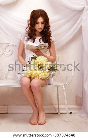 Portrait of brown-haired girl in a white dress, reading a book with a yellow bouquet of flowers on her lap - stock photo
