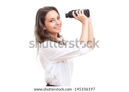 Portrait of brunette beauty holding binoculars isolated on white background.
