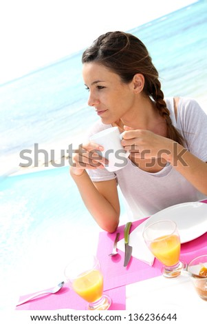 Portrait of brunette girl having coffee by the beach