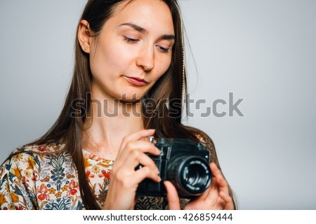 portrait of brunette girl holding retro camera, isolated on gray background